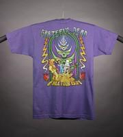 "T-shirt: ""Follow the Golden Road"" - bear, skeleton Dorothy, Tin Man, skeleton scarecrow. Back: ""Grateful Dead / Fall Tour 1994"" stealies, bear, skeleton Dorothy, Tin Man, skeleton scarecrow"