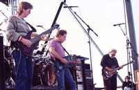 Grateful Dead: Phil Lesh, Bob Weir, and Jerry Garcia, with Bob Bralove in the background offstage