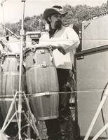 "Ron ""Pigpen"" McKernan at an unidentified outdoor venue playing congas, ca. 1970"