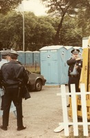 Police officers and porta-potties at an unidentified gathering, ca. 1990