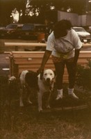 Unidentified photograph, with a dog and a girl near a stack of lumber, ca. 1990