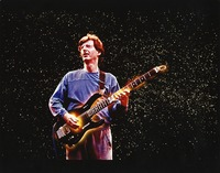 "Phil Lesh, ca. 1990: ""abstracted graphic image"" of Phil Lesh with glowing hands, playing in front of a night sky-like background"