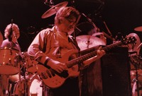 Grateful Dead: Phil Lesh with Bill Kreutzmann and Mickey Hart in the background