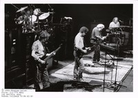 Grateful Dead: Phil Lesh, Bob Weir, Jerry Garcia, and Vince Welnick, with Mickey Hart in the background