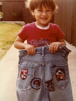 Deadhead's son displaying a pair of jeans with several Grateful Dead patches