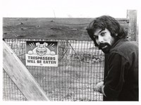 "Mickey Hart at the gate to his ranch, by a ""Trespassers will Be Eaten"" sign"