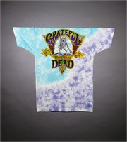 "T-shirt: ""Grateful Dead Brand"". Back: ""Quality Rock and Roll since 1965"" - skeleton drumming"