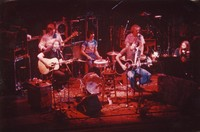Grateful Dead during an acoustic set: Jerry Garcia, Phil Lesh, Mickey Hart, Bob Weir, Bill Kreutzmann, Brent Mydland