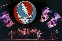 "Grateful Dead, ca. 1990s: distant view of the stage, with reverse image of the ""stealie"" logo by Owsley Stanley and Bob Thomas superimposed"
