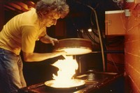 "Lawrence ""Ram Rod"" Shurtliff prepares a tar's drumhead over a hot flame, ca. 1981"
