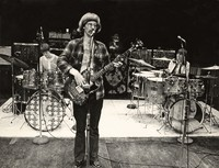 "Phil Lesh with two girls accompanying him on drums, Ron ""Pigpen"" McKernan in background"