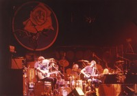 Grateful Dead performing an acoustic set: Phil Lesh, Jerry Garcia, Mickey Hart, Bill Kreutzmann, Bob Weir, Brent Mydland