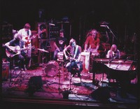 Grateful Dead during an acoustic set: Jerry Garcia, Phil Lesh, Mickey Hart, Bob Weir, Bill Kreutzmann, and Brent Mydland
